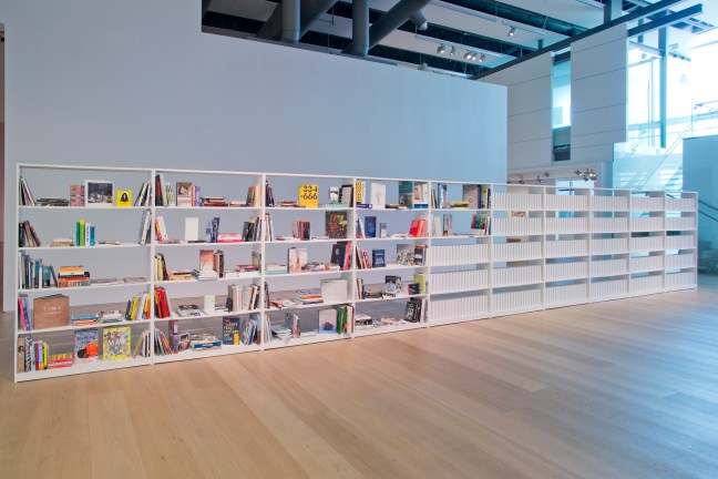 An installation shot of Bilal's 168:01 installation at the Esker Foundation. In a large, open gallery with wood floors and white walls, a long bookshelf is half-full of books. The other half is made up of what looks like empty books with white spines.