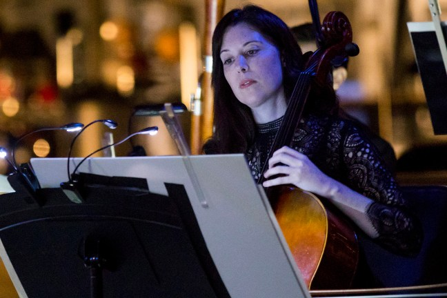 The camera is fixed on Rebecca, who is playing cello in a concert hall, focusing on her sheet music.