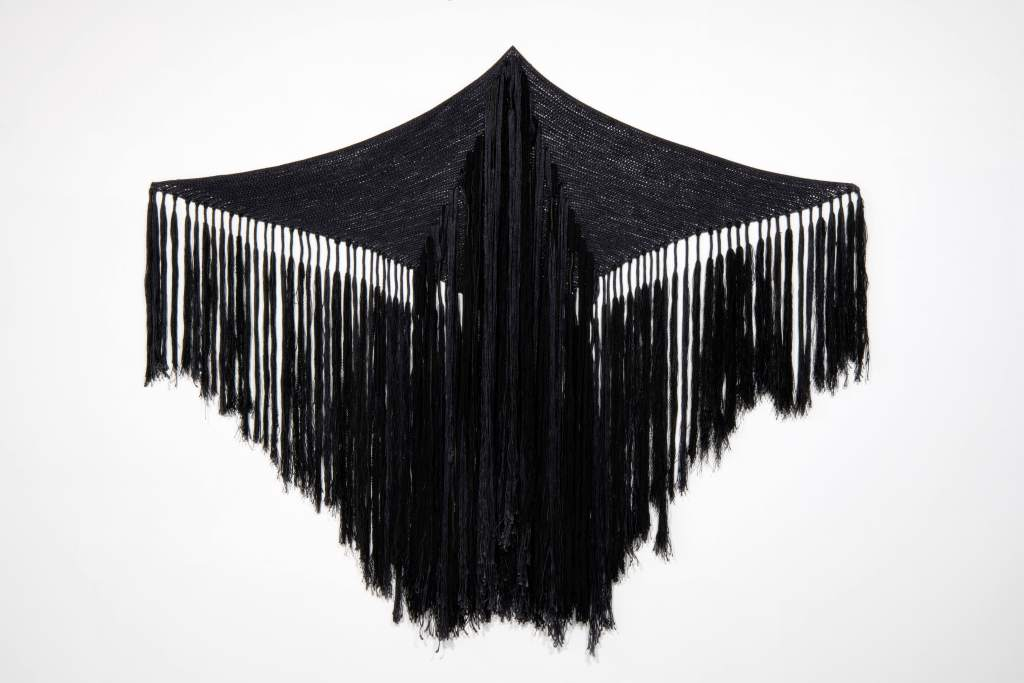A black, diamond-shaped textile with fringe across the middle and bottom hangs open.