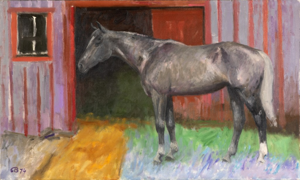 A brown and gray horse stands on top of green, blue, and yellow grass outside a red and purple barn.