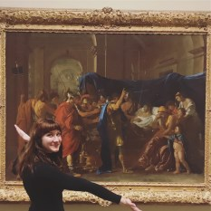 Portrait photo of Laura with her arms open in front of a framed painting at a museum.