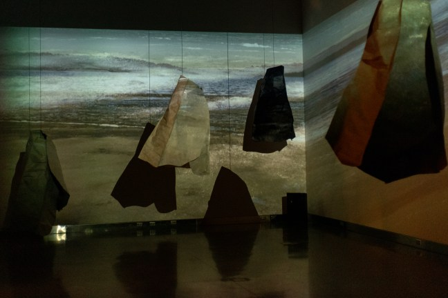 A scene of Rosy's installation: A number of sculptures that resemble sacks hang off the ground from the ceiling. Projected onto them and on the wall behind is a scene of water with waves crashing. The gallery is very dark.