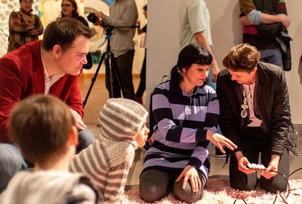 Five figures kneel on a pink carpet in the galleries, inspecting and playing around with a number of tethers that Hiltner has constructed. At the center of the image, Hiltner is demonstrating how the device works.