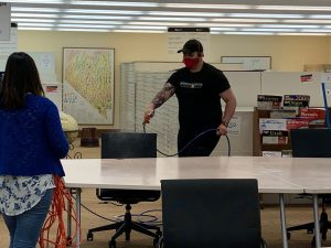 Students sanitizing chairs and tables in map library with approved disinfectant.