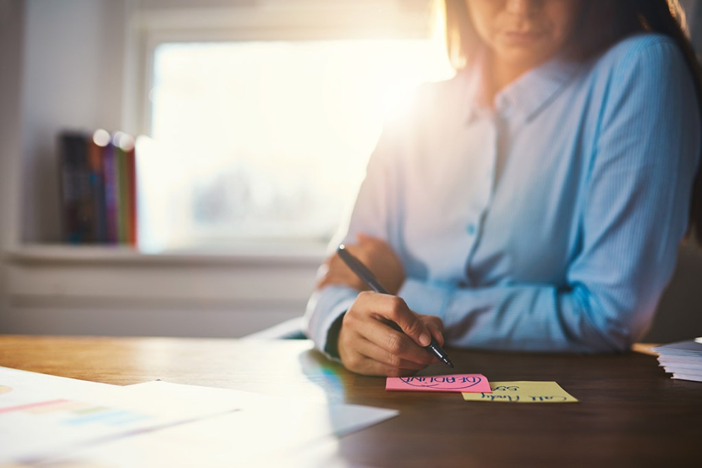 Closeup business woman writing notes on a post it