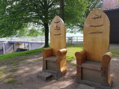 2 grote houten stoelen als kunstproject op de stuw