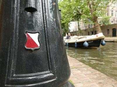 Wapen Utrecht met op de achtergrond een bootje in de gracht