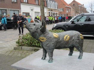 """Het beeld met toepasselijke titel 'Zogge Ku(n)st' voor de kerk van Zogge waar de plaatsnaam Zogge wordt gelinkt aan de benaming zeug voor een vrouwelijk zwijn. Dit dier komt trouwens ook voor op de Zogse feestvlag. Het varken heeft gouden lippen in bladgoud op het varkenslijf. Op het plateau staat volgend geschrift: """"Om je gemoed te sussen, moet je mijn billen kussen. Want zonder zorgen of schulden worden je lippen verguld"""""""