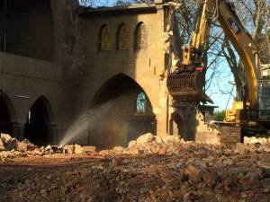 Stuk kerk met sproeier en gele bulldozer