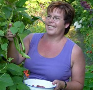 Portret van Joke Vos die fruit aan het plukken is