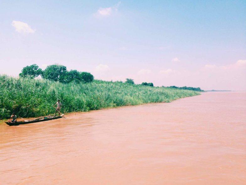 A man rows a sampan over a brown river.