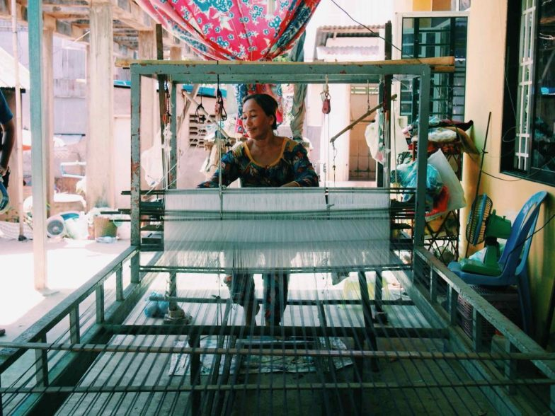 A woman weaves on her backyard loom on Cambodia's Koh Dach island.