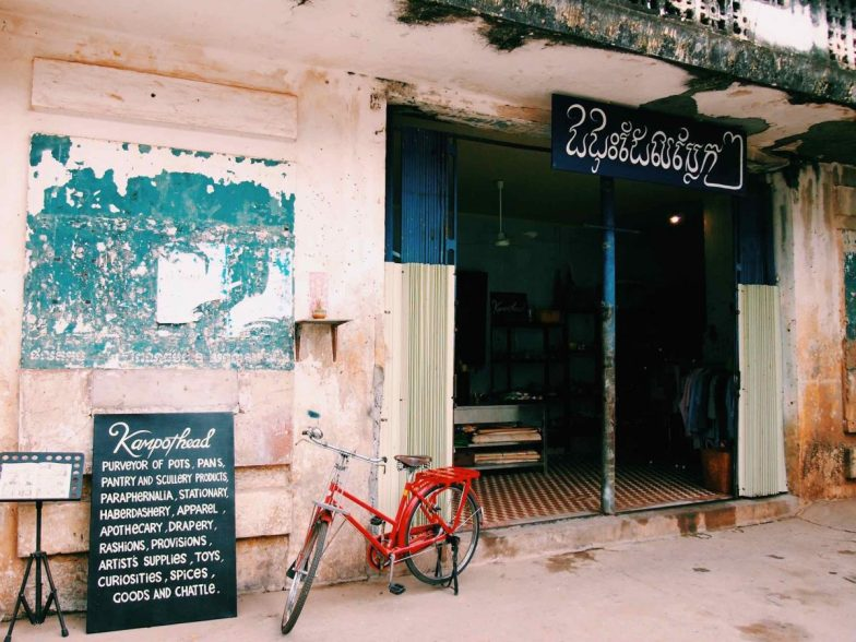 Outside Royal Cinema in Kampot, a red bicycle and a sign advertising a shop.