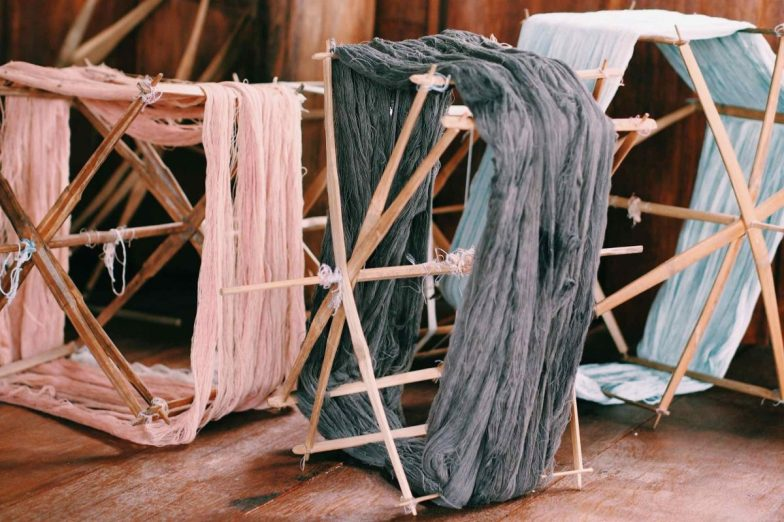 Pink, grey and blue threads on traditional wooden spools at Cambodian Weaving Village.