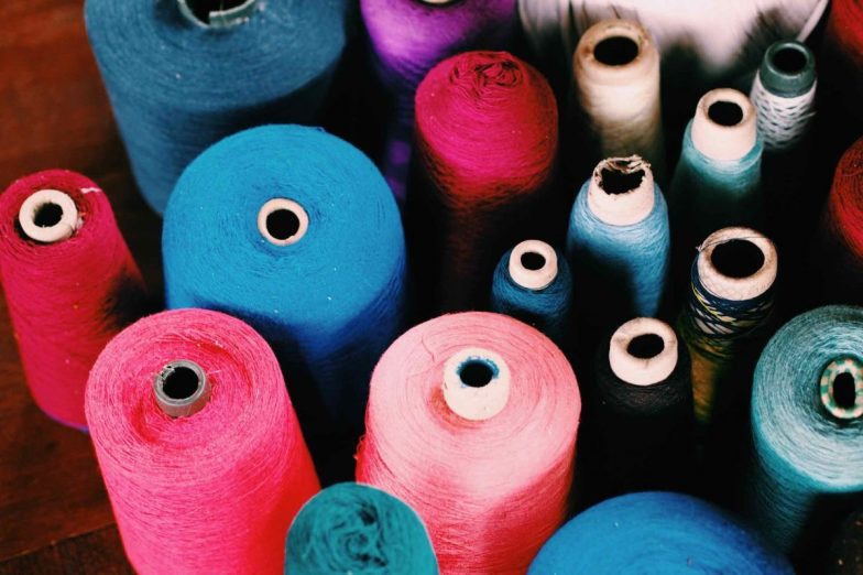 Brightly coloured threads on spools.