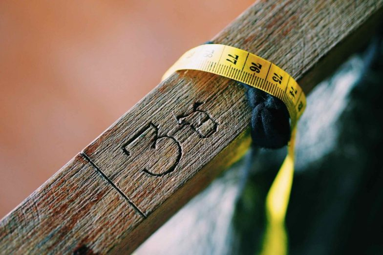 A tape measure wrapped around a piece of wood.