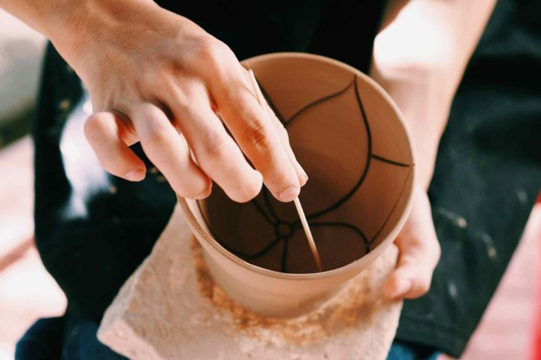 Close up of an artisan engraving a soft clay pot with a toothpick.