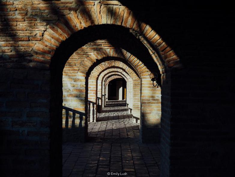 The sun peers through a series of brick archways.