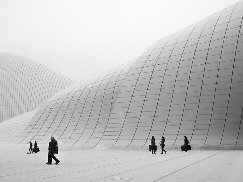 A group of people carrying bags walk in front of the white walls of the Heydar Aliyev Center.