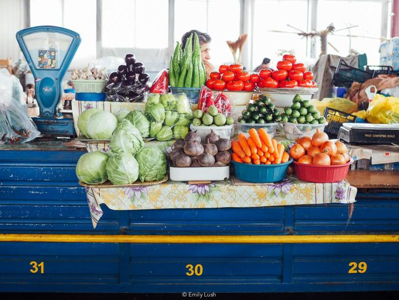 A blue market counter piled high with colourful fresh vegetables.