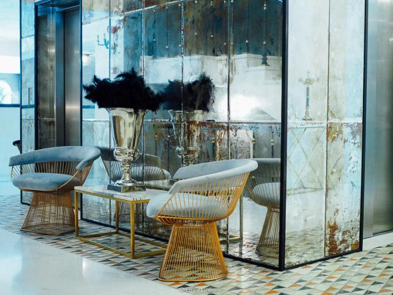 A mirrored lift well with two blue velvet chairs in the lobby of Museum Hotel Orbeliani.