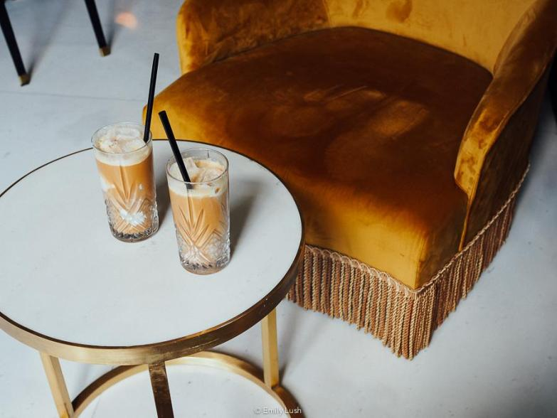 Two tall glasses of iced coffee sitting on a marble table.