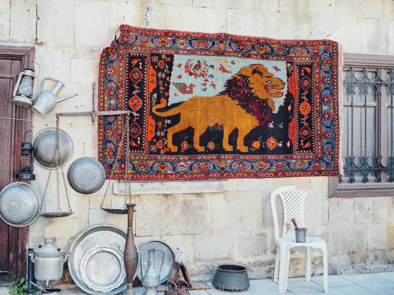 A carpet depicting a lion hangs on a stone wall in Baku Old City.