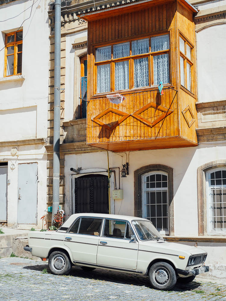 A white car sits on a city street with a wooden picture-box window above it.