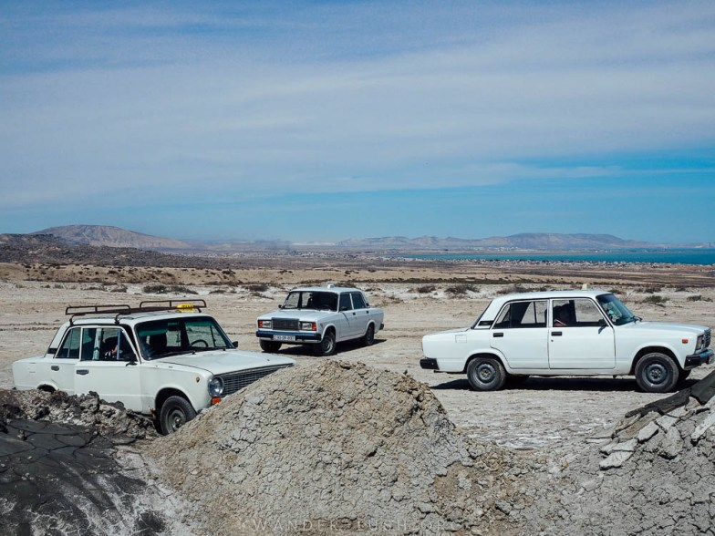 Three white cars in the mud landscape of Gobustan.