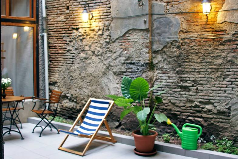 A brick courtyard with a single plant and a blue and white deck chair.