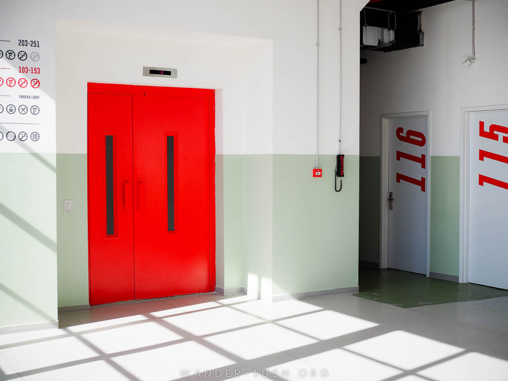 A red elevator door set in a white and green concrete wall.