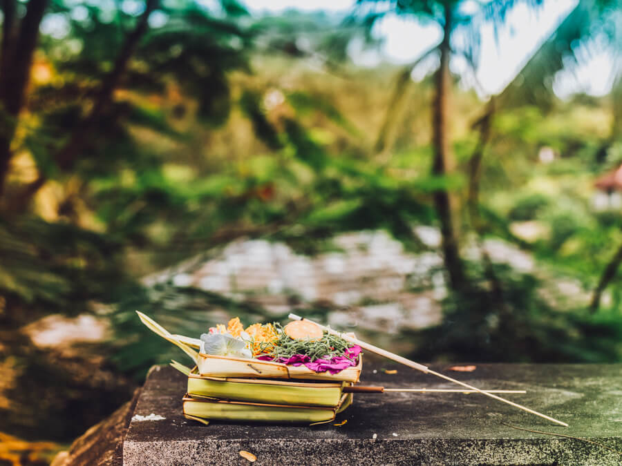 A traditional offering sits on a wooden table in Bali, Indonesia.