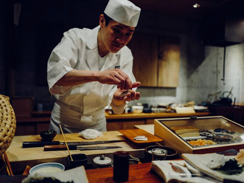 A chef in Japan prepares hand-made sushi at a sushi bar.