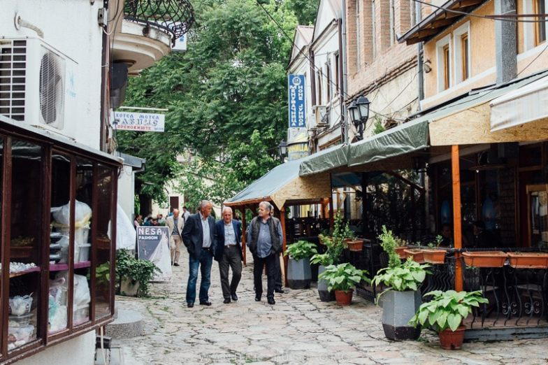 Three men stroll through Skopje Old Bazaar.