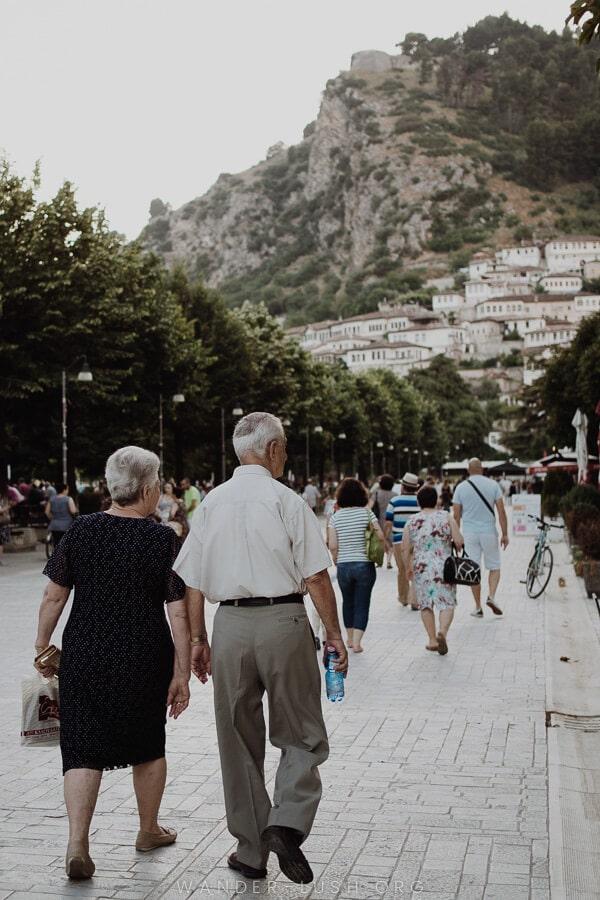 An elderley couple walk along a pedestrian street.
