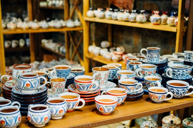 A collection of ceramic cups and plates painted with delicate floral designs.