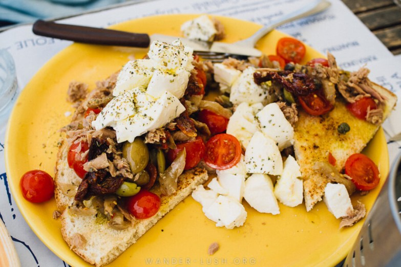 A yellow plate with grilled bread topped with tomatoes, olives and cheese. A traditional food in the Aeolian Islands.