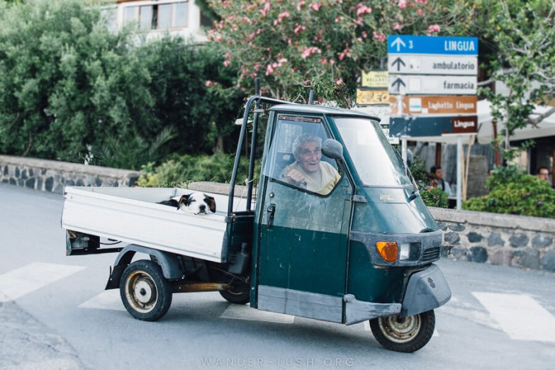 A man in a small green vehicle.