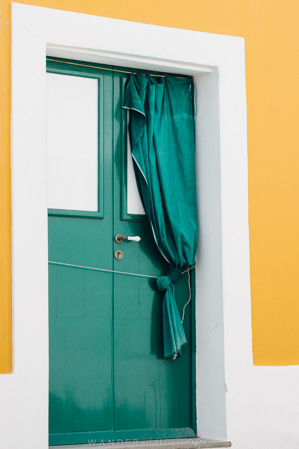 A green door with a matching sash against a yellow and white wall.
