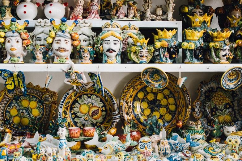Colourful Sicilian ceramics on a white shelf.