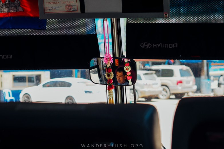 A man's reflection in a bus rearview mirror on the Bangkok to Siem Reap bus.