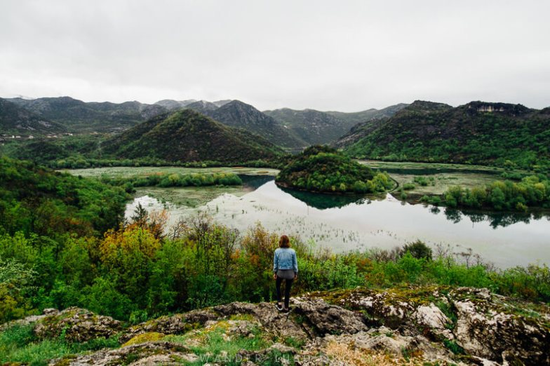 A person looking out over a river and low green hills.
