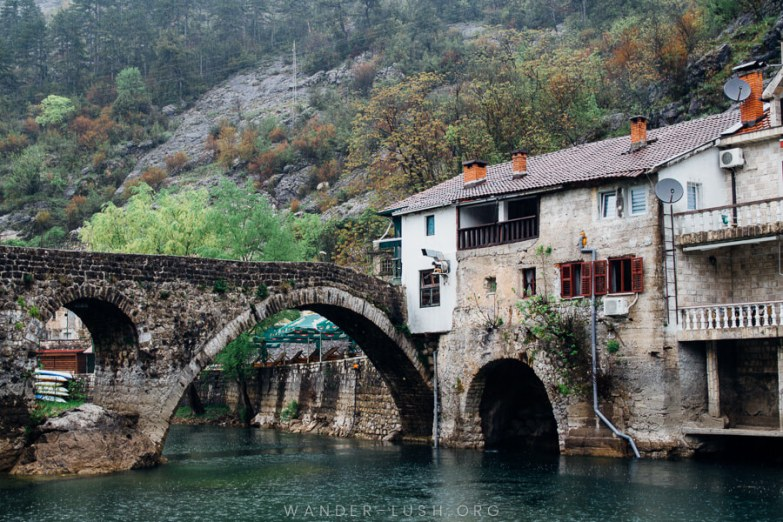 A very old stone bridge and stone houses overhanging a river.
