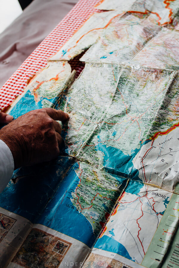 An old hand pointing at something on a map. Planning a Montenegro road trip.
