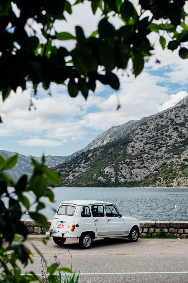 A retro white car parked in front of the ocean with a grey mountain in the background.