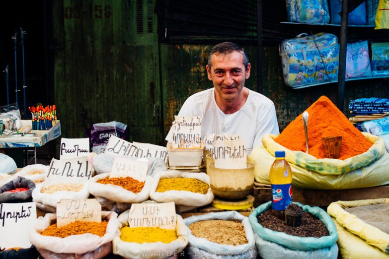 A man in a white shirt sitting behind a market stall selling spices in Gyumri.