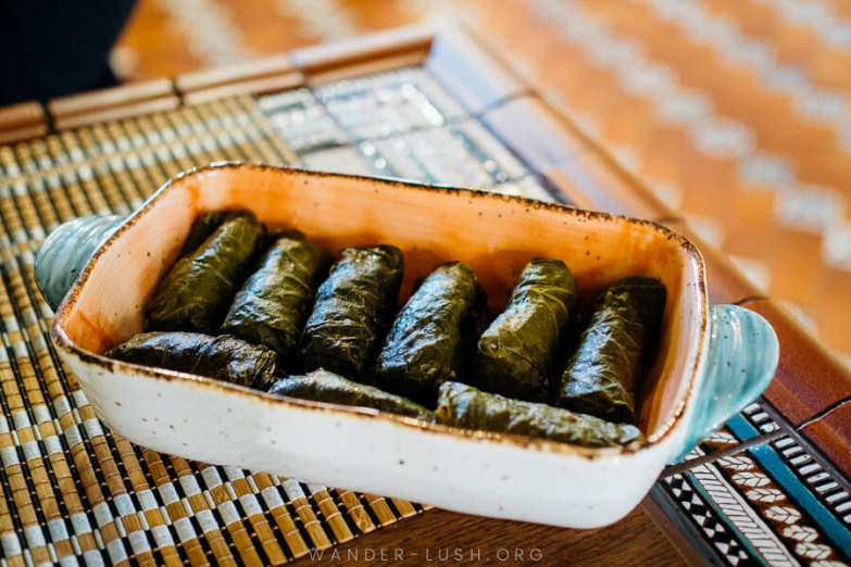 Pork wrapped in vine leaves and served in a ceramic dish.