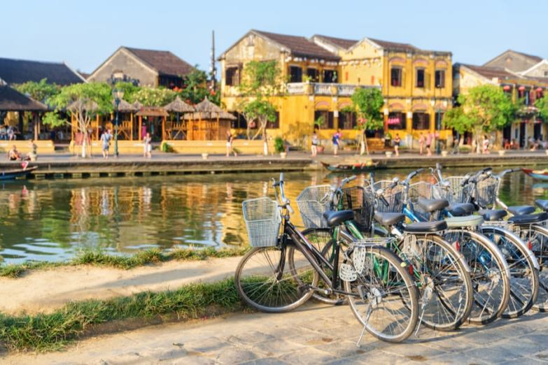 A set of bicycles parked along a waterway with yellow buildings in the background.