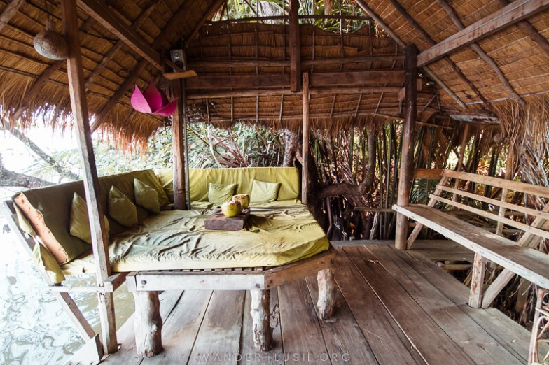 A green day bed inside a rustic bamboo shack.
