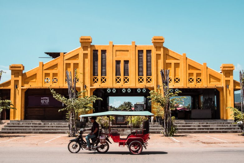 A red tuk tuk sits in front of a yellow market building on the waterfront in Kampot, Cambodia.